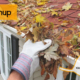 Gloved hand scooping leaves out of gutter, gutters r us logo, fall cleanup blog title